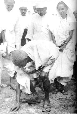 Gandhi collecting salt in an act of civil disobedience